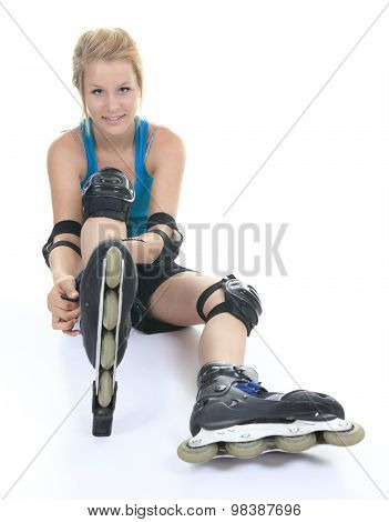 A blond woman posing in studio wearing inline rollerskates