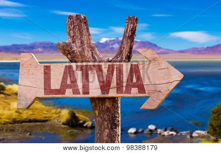 Latvia wooden sign with a beautiful view on background