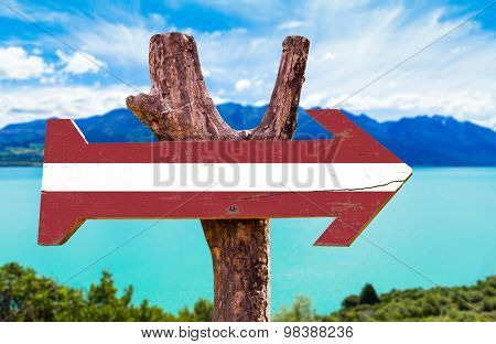 Latvia Flag wooden sign with river on background