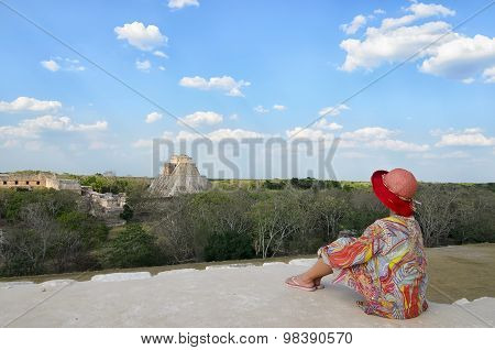 UXMAL, MEXICO, 20 APRIL 2015: Anonymous Woman in colorful dress and red hat sitting on the edge and looking at Mayan pyramids
