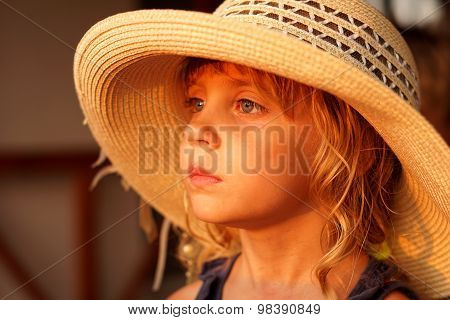 The little girl in a straw hat looks afar