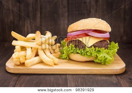 Cheeseburgers With French Fries On Wooden Background
