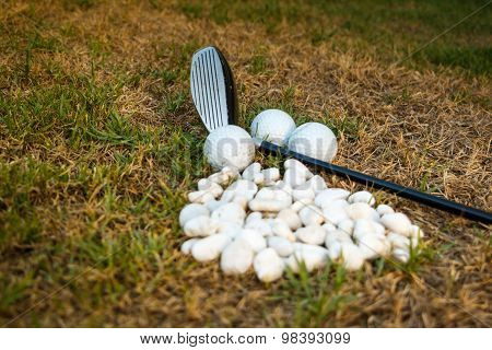 Golf Ball And Golf Club Beside Mini Stone On The Grass