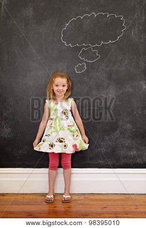 Cute Young Girl In Front Of Chalkboard With A Thinking Bubble