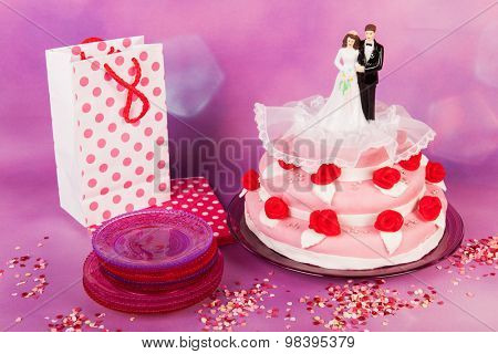 Pink wedding cake with red roses and couple on top