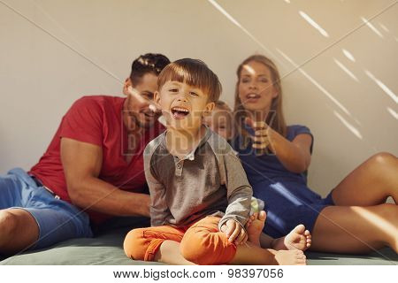 Happy Little Boy Sitting On Patio With His Family