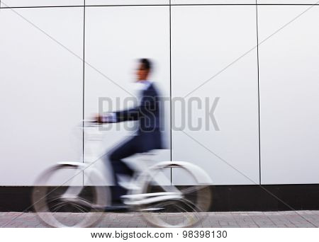 Businessman in suit riding bicycle in urban environment