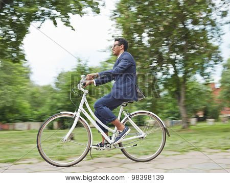 Modern businessman riding bicycle in park