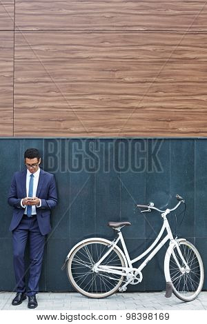 Handsome businessman reading sms while standing by modern building with bicycle near by