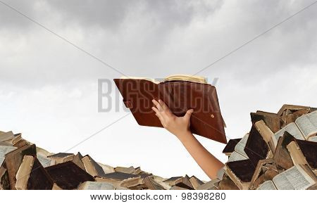 Hand with book reaching out from pile of old books
