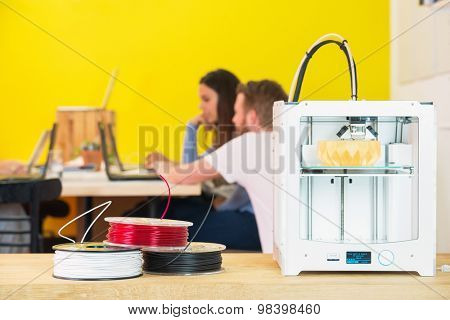 3D printing machine with product on counter with designers discussing in background at creative studio