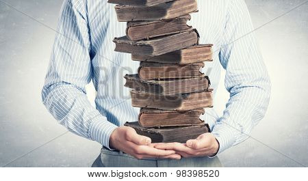 Close up of man holding pile of books in hands