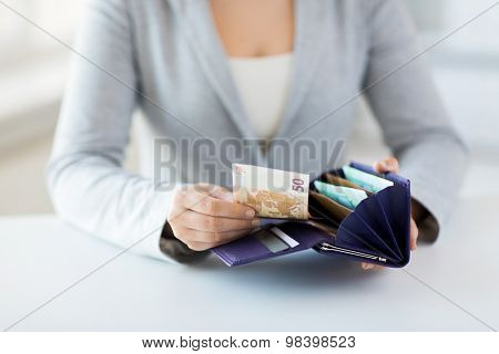 business, finance, saving, banking and people concept - close up of woman hands with wallet and euro money