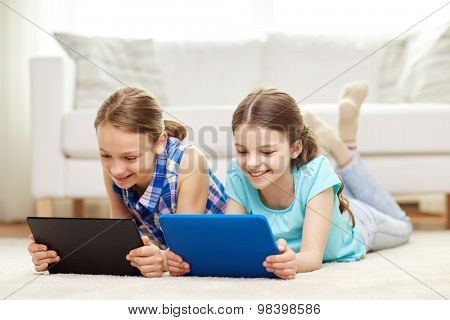 people, children, technology, friends and friendship concept - happy little girls with tablet pc computers lying on floor at home