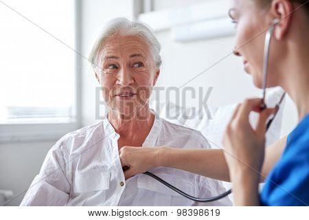 medicine, age, support, health care and people concept - doctor or nurse with stethoscope visiting senior woman and checking her breath or heartbeat at hospital ward