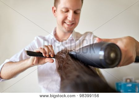 beauty, hairstyle, blow-dry and people concept - close up of hairdresser with hair dryer and brush making hot styling at salon
