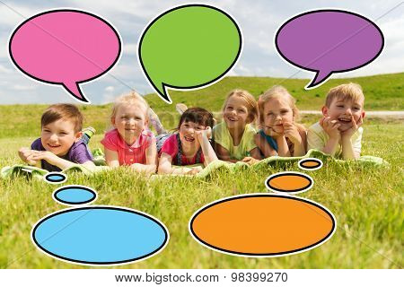 summer, childhood, leisure and people concept - group of happy kids lying on blanket or cover outdoors with colorful text bubble icons