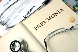 stock photo of pneumonia  - Word  Pneumonia on a paper and pills on the wooden table - JPG