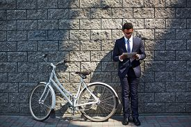 stock photo of employee  - Handsome employee with touchpad networking by wall of modern building with bicycle near by - JPG