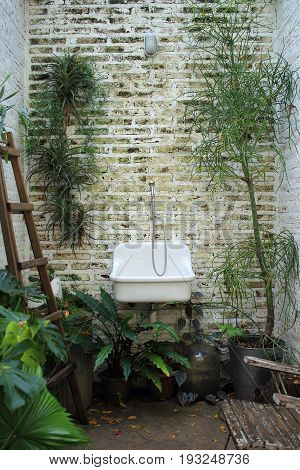Image of old sink on brick background