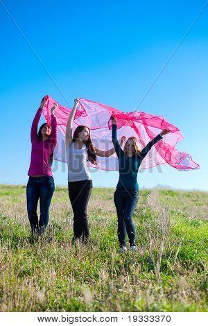 Drei junge schöne Frau stehend mit Gewebe ins Feld gegen den Himmel