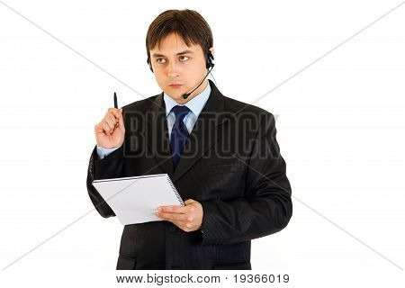 Pensive businessman with headset holding notebook in hand isolated on white