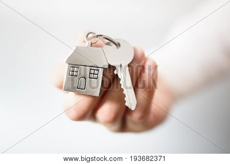 Holding house keys on house