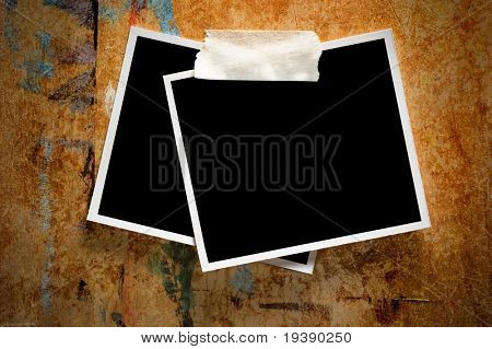 Two instant photo frames on a grungy wooden background