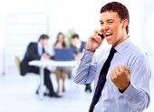 stock photo of woohoo  - One very happy energetic businessman with his arms raised - JPG
