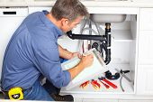 stock photo of plumber  - Young smiling plumber repairing sink in kitchen - JPG