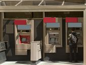 stock photo of automatic teller machine  - Person accessing Automatic Teller Machine daylight atm - JPG