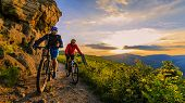 Mountain biking women and man riding on bikes at sunset mountains forest landscape. Couple cycling M poster