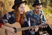 Attractive Female In Black Summer Hat Playing Guitar With Great Pleasure Singing Songs To Her Boyfri poster