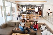 People Sitting On Sofa And Watching TV In Busy Family Household poster