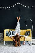 Home portrait of pre teen child girl wearing pajama relaxing and chilling on the yellow couch agains poster