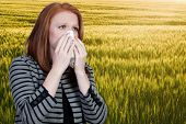 picture of hay fever  - A beautiful woman with a cold hay fever or allergies blowing her nose - JPG