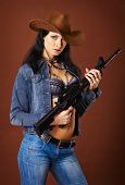 pic of saxy  - A beautiful young woman with a rifle on a brown background - JPG