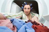 a woman reaching in the dryer for clothes - domestic series poster