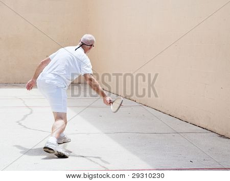 Senior man working out on a racquetball court.