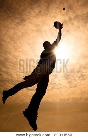 The silhouette of baseball player jumping into air to make the catch