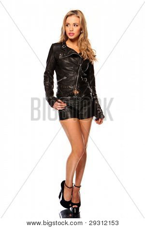 Young woman in leather and shorts looking shyly to her right
