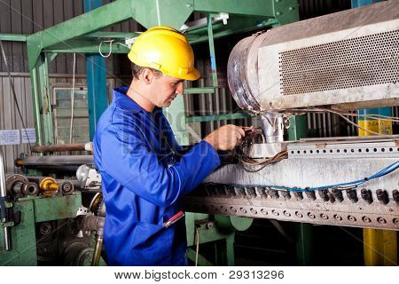 industrial mechanic repairing heavy industry machine in plant