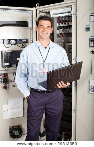 modern factory technician in front of industrial machine