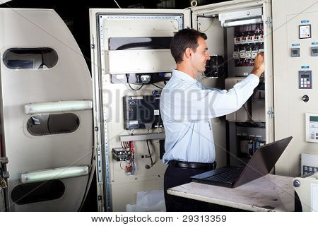 technician repairing industrial machine with laptop computer