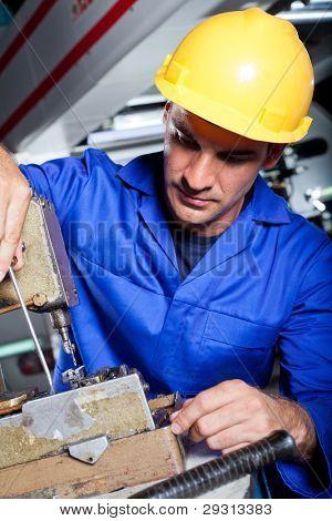 factory mechanic repairing industrial sewing machine