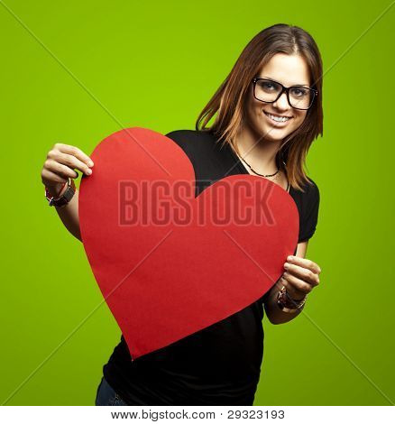portrait of a pretty woman holding a paper heart against a green background