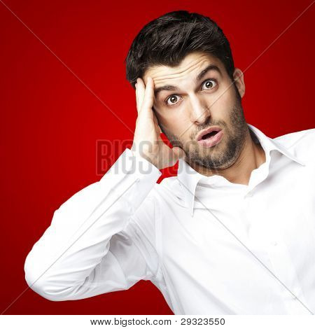 portrait of young man surprised against a red background