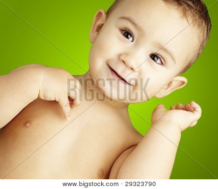 portrait of happy kid shirtless smiling and posing over green background