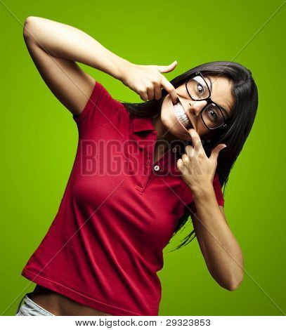portrait of happy young woman doing a grimace over green background