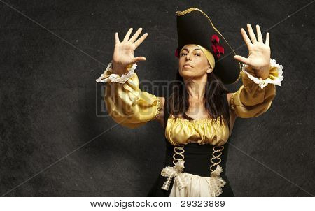 portrait of pirate woman gesturing stop against a grunge background